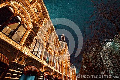 Festive illuminations in streets of city. New Year and Christmas lights decoration in snowy night, Red Square, Moscow, Russia.
