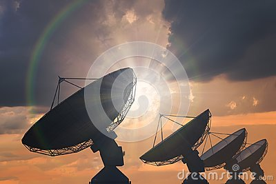 Silhouettes of array of satellite dishes or radio antennas at sunset