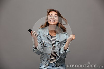 Happy young woman in jeans jacket clenching her fists in winner