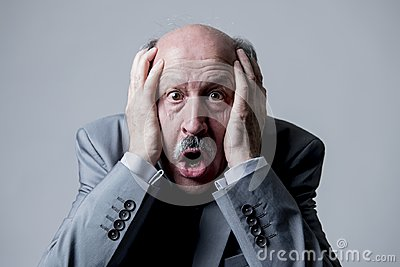 Close up head portrait of bald 60s senior business man surprised and scared looking as if big mistake or disaster in the office