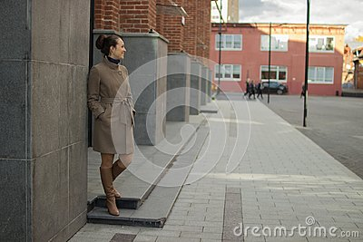 Young woman in a beige coat stands near a brick wall