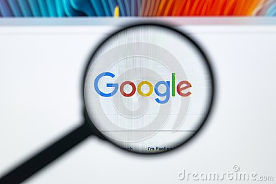 Google homepage on the Apple iMac monitor screen under a magnifying glass. Google is world`s most popular search engine