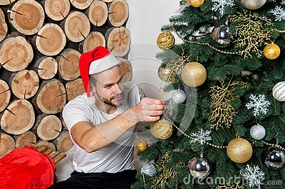 Man in santa claus hat decorate Christmas tree