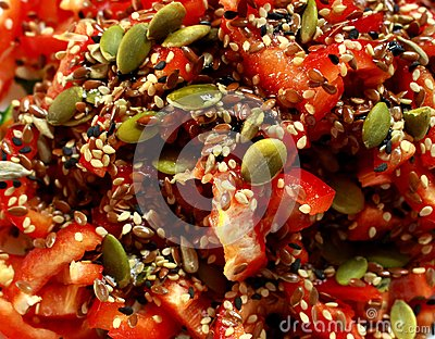 Bright tomato salad with colorful sunflower seeds as fresh healthy vegeterian food background.