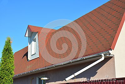 Roof Asphalt Shingles with Moss. Rain Gutter Pipeline with Downspout Pipe and Attic Mansard Window.