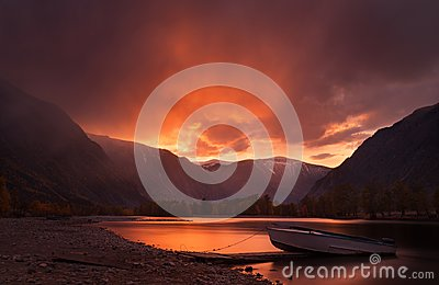 Sunset In The Mountains. Enchanting Autumn Mountain Landscape In Red Tones With Sunset Sky, River with Reflection And Lonely Boat.