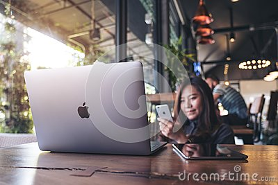 November 17th 2017 : Asian business woman holding smart phone with laptop on wooden table in modern cafe , Chiangmai Thailand