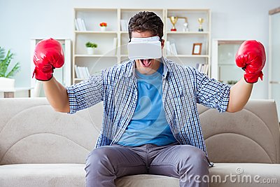 d3b84e8417ae The man wearing virtual reality vr glasses playing boxing game