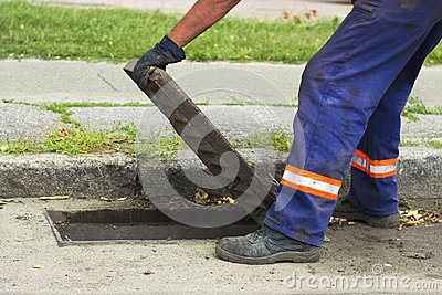 Worker hands opens a drain grate close-up