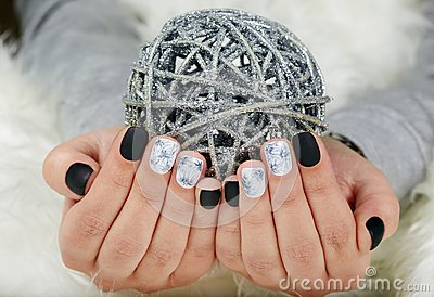 Hands with manicured nails colored with black and white nail polish