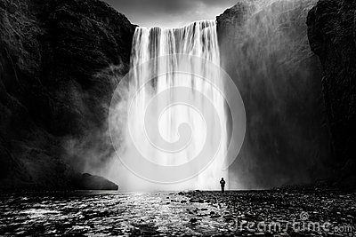 Skogafoss waterfall with a lonely man