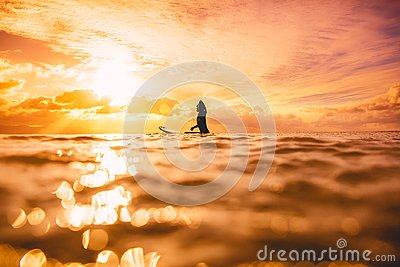 Sporty surf woman in sea at sunset or sunrise. Winter surfing in ocean