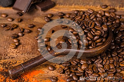 Dark roasted pure arabica coffee beans and ground coffe on the w