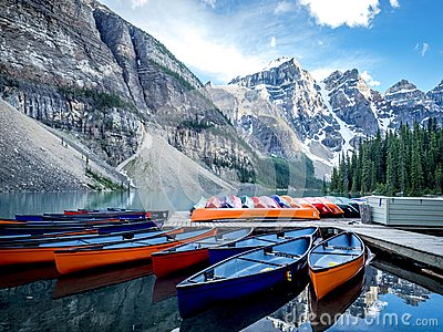 SEVERAL CANOES ON A DOCK ON LAKE MORAINE WITH MOUNTAIN BACKGROUND