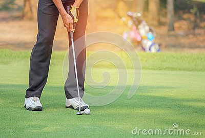 Golfer in action putting golf ball on the green grass near the hole