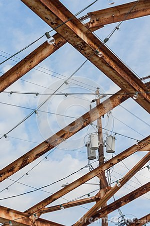 Power pole and transformers set against a blue sky, seen through rusted girder roof system