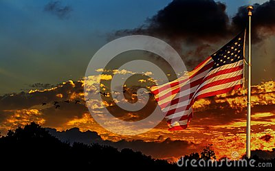 American flag on flagpole waving in the wind American flag in front of bright sky