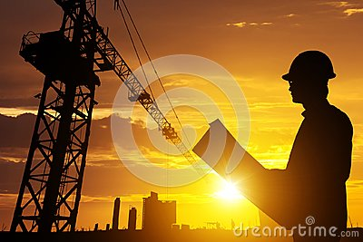 Silhouette Businessman engineer looking blueprint in a building site over Blurred construction site film grain progress and potent