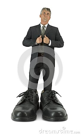 Some big shoes to fill man standing in giant shiny business footwear
