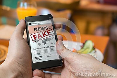 Man is holding smartphone and reading fake news on internet. Propaganda, disinformation and hoax concept