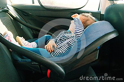 stock image of baby smile in a safety car seat. security. one year old child girl in blue wear sit on auto cradle. rules for the safe transport o