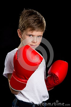 An angry, confident boxer with red gloves. The defend position portrait on the black background