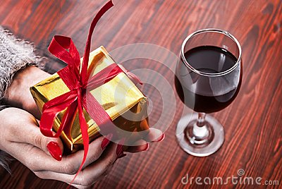 Female hand holding golden box present with red bow on wooden background and wine glass on table