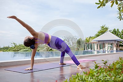 Woman playing healthy yoga beside outdoor swimming water pool