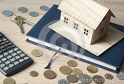 Home savings, budget concept. Model house, notepad, keys, calculator and coins on wooden office table.