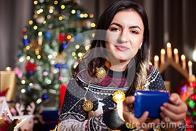 Portrait of brunette woman holding a blue gift box in hands
