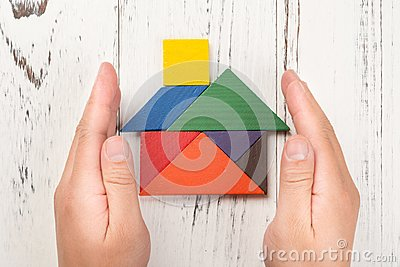 Hands surround a wooden house made by tangram home insurance concept and representing home ownership