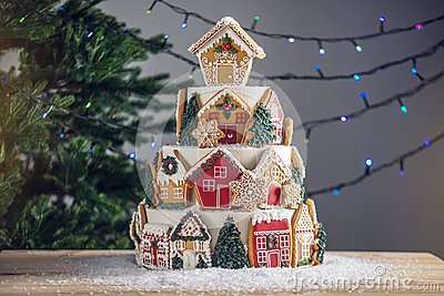 Large tiered Christmas cake decorated with gingerbread cookies and a house on top. Tree and garlands in the background.