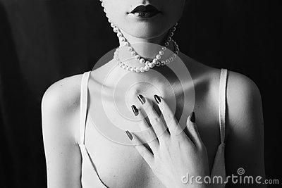 The long neck and beautiful clavicle. Woman wearing a necklace of beads on a black background. Red-haired girl with red lips, pale