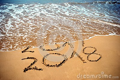 New Year 2018 is coming concept - inscription 2017 and 2018 on a beach sand, the wave is covering digits 2017. New Year 2018 celeb