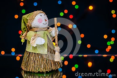 Snowman with a broom on a background of colored lights
