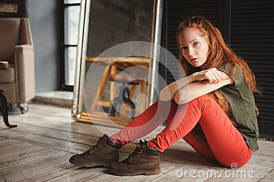 Indoor portrait of beautiful young redhead woman