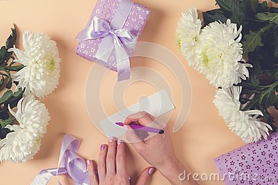 Woman hand writing a note with the text thank you on a pape