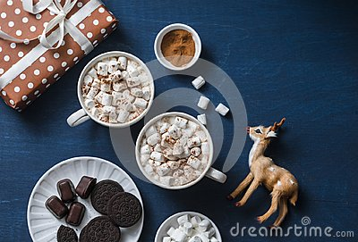 Christmas inspiration table - hot chocolate with marshmallows, cookies, gift box, christmas ornament reindeer on a blue background