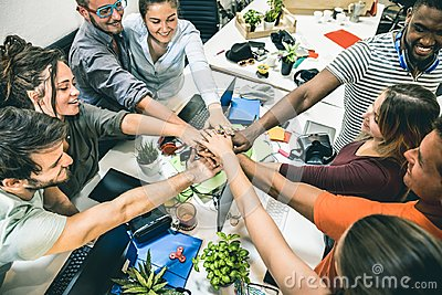 Young employee startup workers group stacking hands at start up office