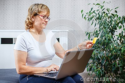 Old people and modern technology concept. Portrait of a 50s mature woman hand holding credit card, using online internet payment a