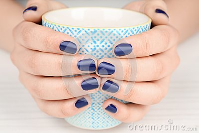 Nail art concept. Beautiful female hands with neat manicure holding cup