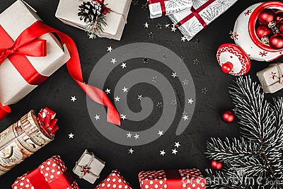 Upper top view of a red ribbon, Christmas presents, tree toys, sparkling stars and evergreen branch on a stone black background.