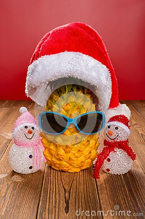 Pine apple wears a santa claus hat and sun glasses with two snowmen