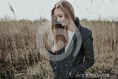 Blonde Woman in wool coat at meadow
