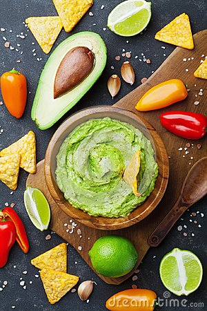 Avocado guacamole with ingredients pepper, lime and nachos on black table top view. Traditional mexican food.