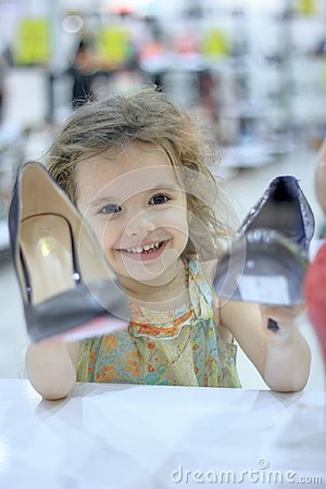 Little kid girl in a shoes store with the shoes on a shop-window.