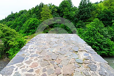 The stone arched bridge over the mountain river in Georgia