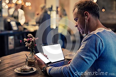 Man using tech gadgets in cafe