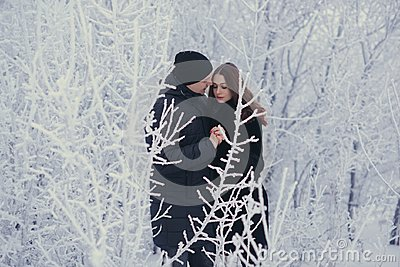 A loving couple on a winter walk. Snow love story, winter magic. Man and woman on the frosty street. The guy and the girl are rest