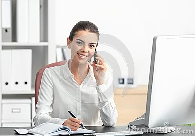 Young female receptionist talking on phone